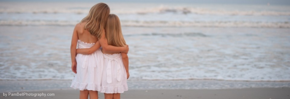 as-sisters-hugging-on-beach-960