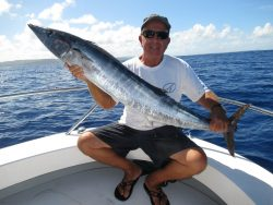 guy holding a wahoo fish he caught