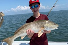 Kid holding a fish he caught on Amelia Island