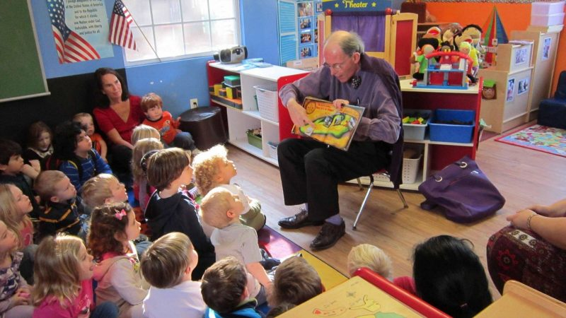 Man reading to young kids in a classroom