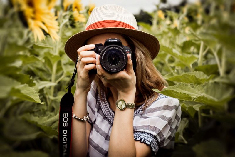 woman holding a camera in flowers
